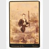 Photograph of Boy Sailor in Boat | Period: c1920 | Make: Mathewson & Co, Brisbane | Material: Sepia photograph on board.