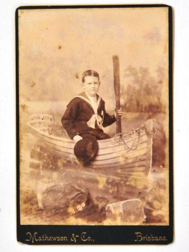 Photograph of Boy Sailor in Boat   Period: c1920   Make: Mathewson & Co, Brisbane   Material: Sepia photograph on board.
